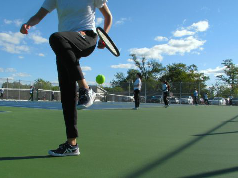In order to follow 冠状病毒病-19 guidelines, members of the girls 网球 team must pick up balls during practice 通过 capturing the ball in between their foot and their racquet, lifting their leg to bounce the ball, and finally catching the ball with their racquet.